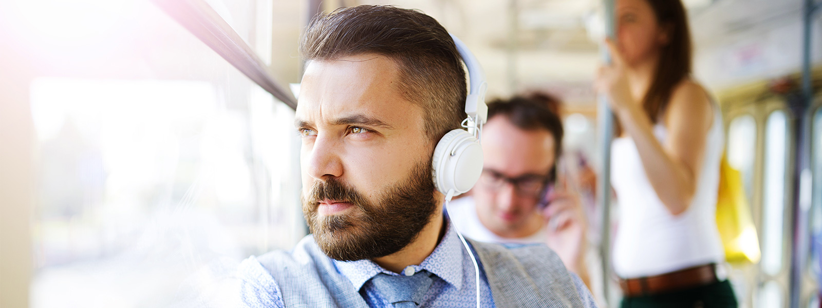 Bearded young professional in headphones looking out the window
